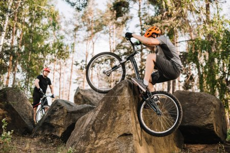 extreme trial bikers riding on rocks outdoors