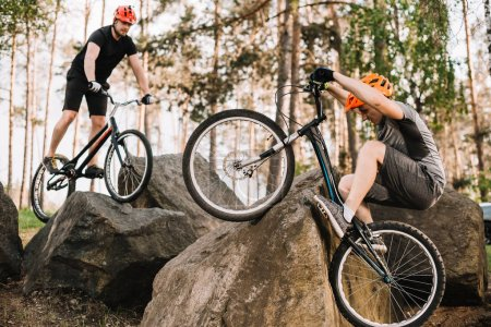 athletic young trial bikers riding on rocks outdoors