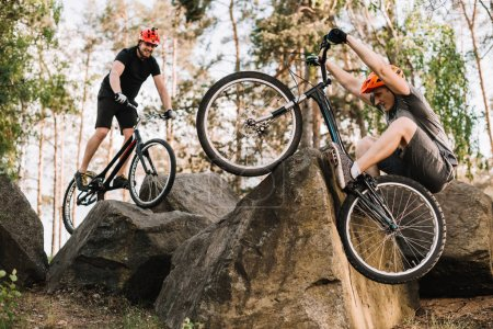 active young trial bikers riding on rocks outdoors