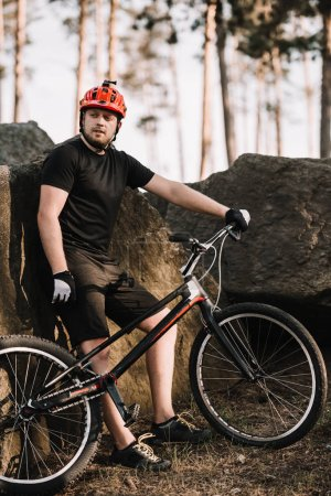 handsome young trial biker leaning back on rocks outdoors in forest and looking at camera