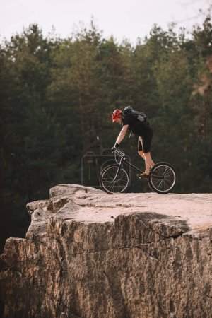 side view of trial biker balancing on rocky cliff outdoors