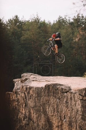 trial biker jumping on bicycle over rocky cliff outdoors