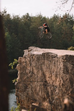 trial biker jumping on bicycle over rocky cliff outdoors in forest