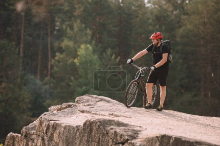 Photo for Young trial biker standing on rocky cliff outdoors and looking away - Royalty Free Image