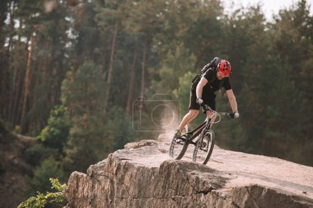 Photo for Young trial biker riding on rocky clifff outdoors - Royalty Free Image
