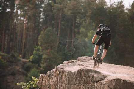 back view of young trial biker riding on rocks outdoors