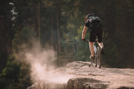 rear view of young trial biker riding on rocks outdoors