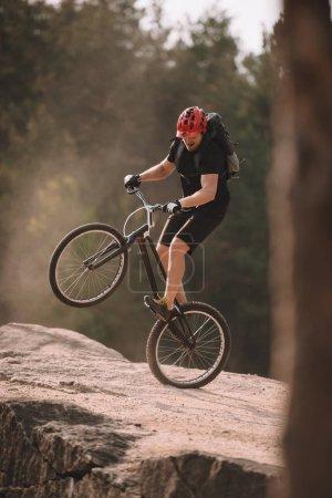 Photo pour Beau motard d'essai équilibrage sur la roue arrière sur les rochers à l'extérieur - image libre de droit