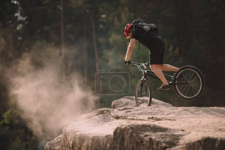 young trial biker balancing on front wheel on rocks outdoors