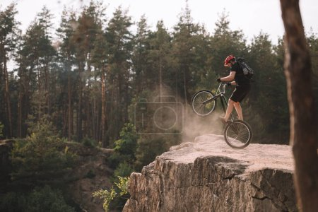 trial biker balancing on back wheel on rocks outdoors