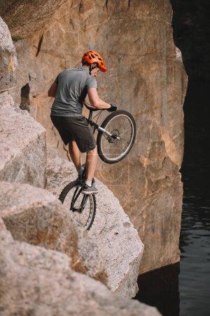 Photo pour Vue d'angle élevé d'essai motard en équilibre sur la roue arrière sur les rochers à l'extérieur - image libre de droit