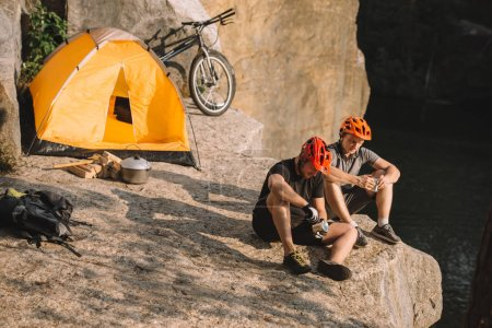 young bike travellers with canned food sitting on cliff