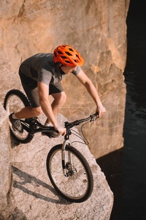 high angle view of young trial biker balancing on rocks outdoors