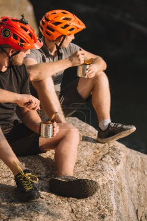 active travellers eating canned food on rocky cliff