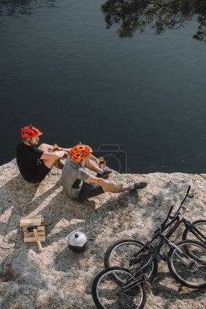 high angle view of young trial bikers eating canned food on rocky cliff