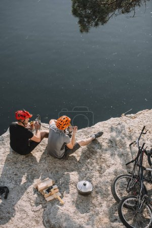 high angle view of bike travellers eating canned food on rocky cliff over lake