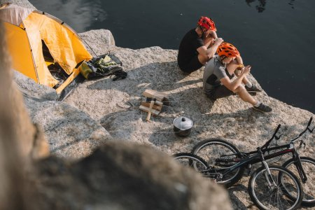 high angle view of active bike travellers eating canned food in camping on rocky cliff