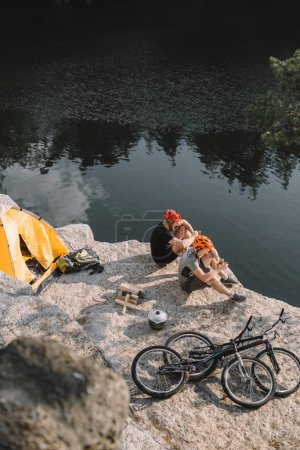 high angle view of young bike travellers eating canned food in camping on rocky cliff