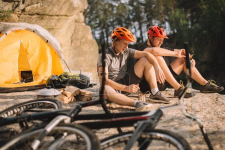 young trial bikers eating canned food in camping outdoors