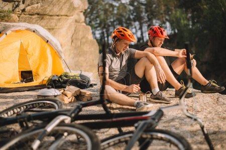 Photo pour Jeunes motards d'essai manger de la nourriture en conserve dans le camping en plein air - image libre de droit