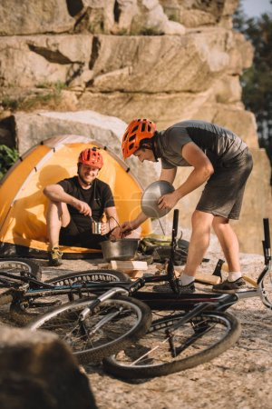 young trial bikers cooking food on camping outdoors