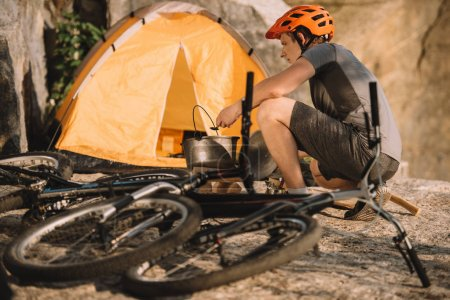 young trial biker at camping with bicycles outdoors