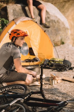 athletic young bike traveller sitting on rocks with camping tent and blurred friend sitting on background