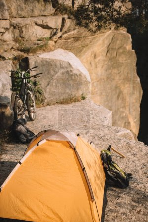 camping tent with trial bikes and backpack on rocky cliff