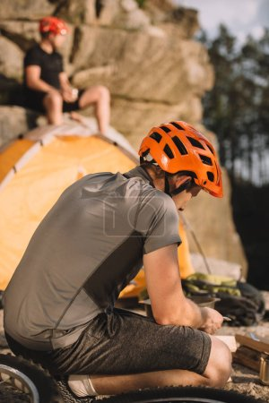 young bike traveller sitting on rocks with camping tent and blurred friend sitting on background