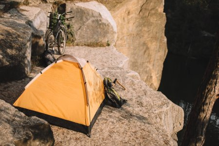 camping tent with trial bikes and backpack on beautiful rocky cliff