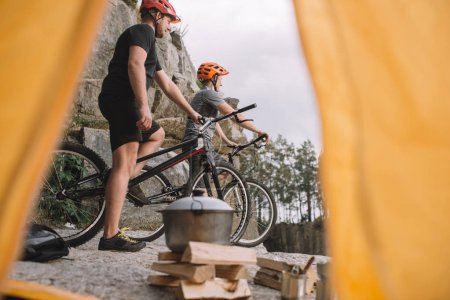 view of athletic trial bikers on rocky cliff outdoors from camping tent