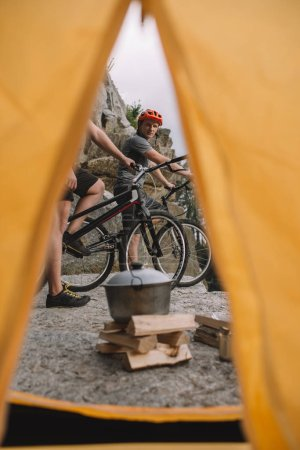 view of trial bikers on rocky cliff outdoors from camping tent