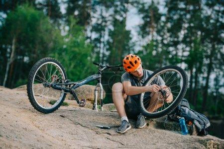 young trial biker examining bike wheel outdoors