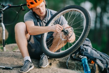 serious young trial biker fixing bicycle wheel outdoors while sitting on stone