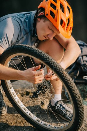 close-up shot of young trial biker fixing bicycle wheel outdoors