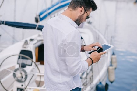 back view of man in sunglasses using digital tablet near yacht