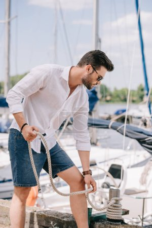 handsome young man in sunglasses holding rope while standing near yacht