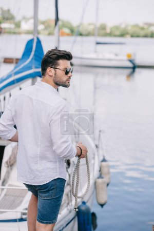 handsome young man in sunglasses looking away while holding rope at yacht