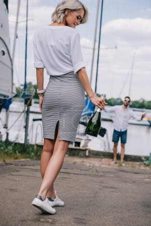 smiling stylish girl holding bottle of wine and going to handsome man waiting near yacht