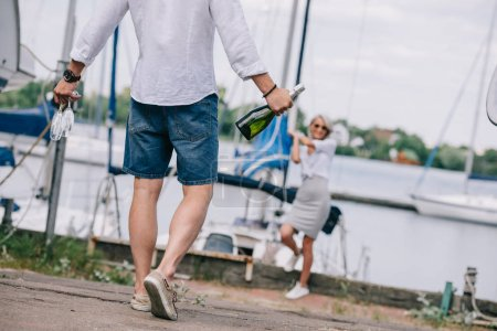 cropped shot of man holding wine glasses and bottle while happy girl standing near yacht