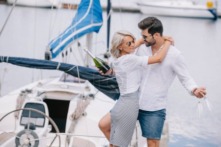 smiling girl in sunglasses hugging handsome man with wine bottle and glasses on yacht