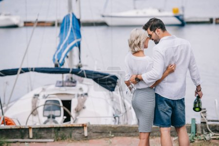 happy young couple with wine bottle and glasses hugging while standing near yacht