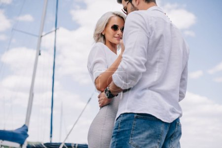 low angle view of beautiful stylish young couple in sunglasses hugging on yacht