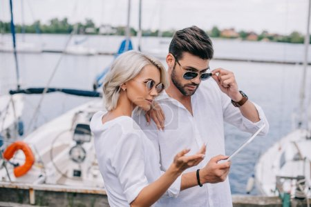 beautiful stylish young couple in sunglasses using digital tablet on yacht
