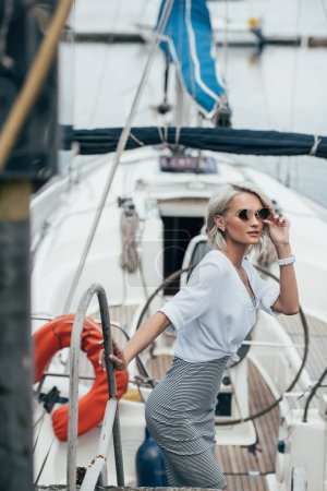 beautiful young woman in sunglasses looking at camera on yacht