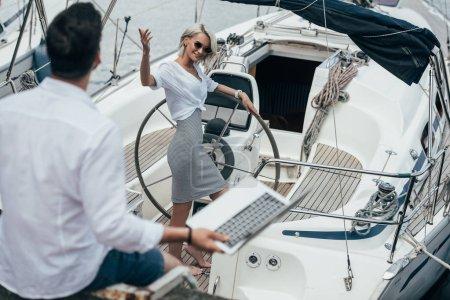 Photo pour Vue d'angle élevé de jeune fille souriante au volant en agitant la main et en regardant de jeune homme sur yacht - image libre de droit