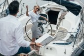 high angle view of smiling girl at steering wheel waving hand and looking at young man on yacht
