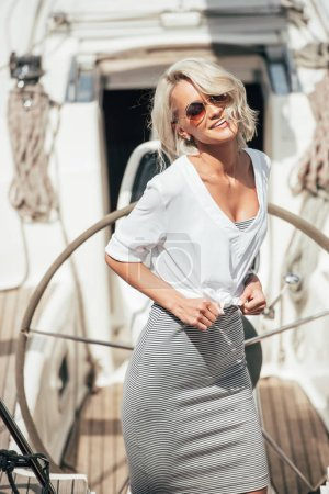 beautiful blonde girl in sunglasses smiling at camera on yacht