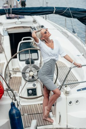 beautiful smiling blonde woman in sunglasses posing near steering wheel on yacht