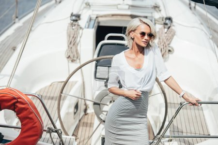 Photo for Beautiful young blonde woman in sunglasses standing on yacht - Royalty Free Image